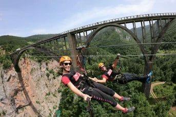 Couple holding hands ziplining next to the bridge