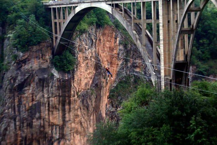 11Woman in jeans ziplining next to the bridge