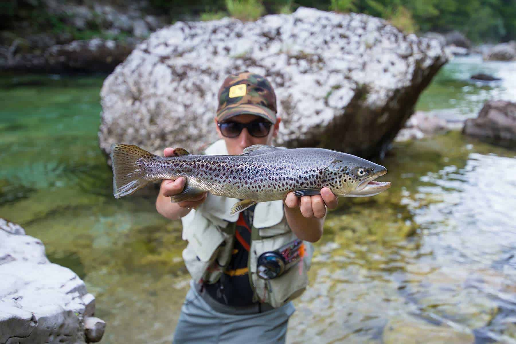Fisherman holding a brown trout in river