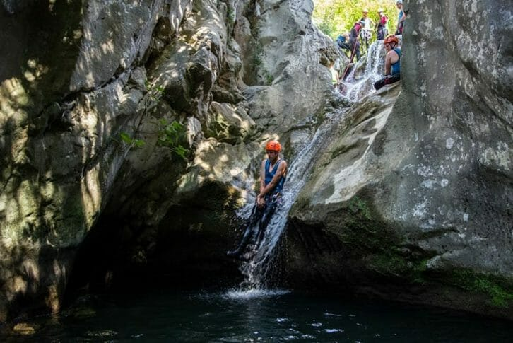 11Group sliding down tiny waterfall during canyoning in Rikovac