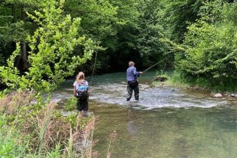 Two people fly fishing in stream on tara river in Montenegro