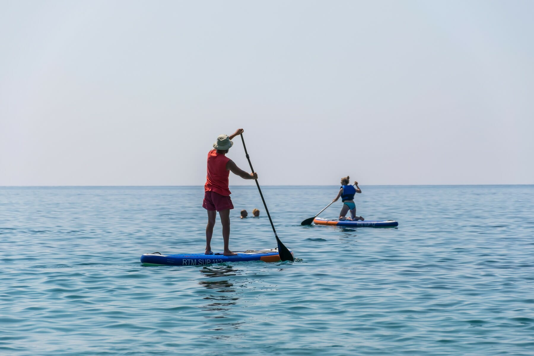 Tourists are engaged in rowing on the board (sup) on the surface of the calm sea 2
