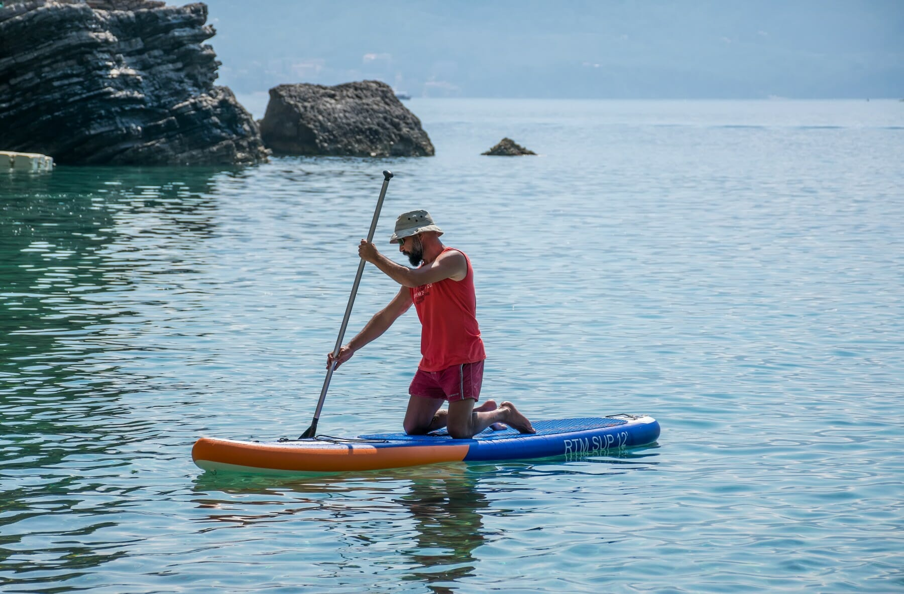 Tourists are engaged in rowing on the board (sup) on the surface of the calm sea