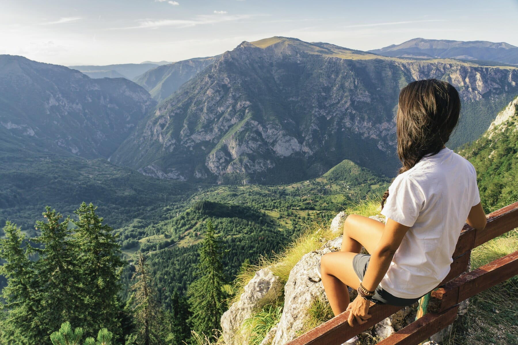 Girl sitting on wooden fence surrounded by hugh peaks of Durmitor Mountain Montenegro