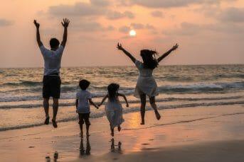Family jumping on the shore of Adriatic Sea sunset Ulcinj Montenegro