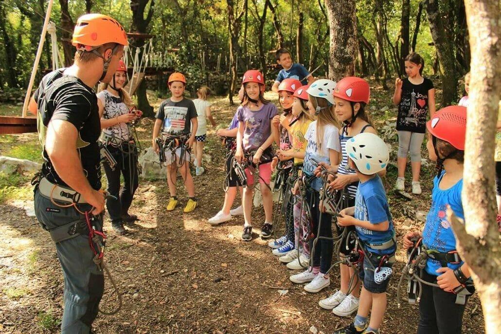 Preparations of a group of kids for zip line in Adventure Park at Konavle