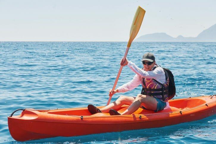 11Boat kayaking near cliffs on a sunny day.
