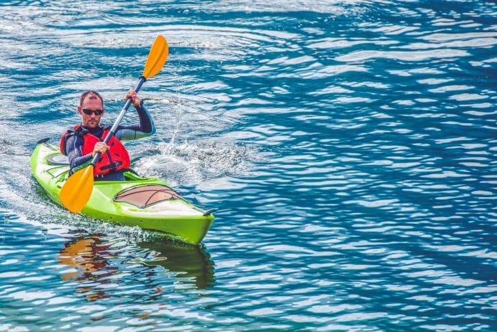11Kayak Tour. Caucasian Men Paddling in the Kayak on the Lake.