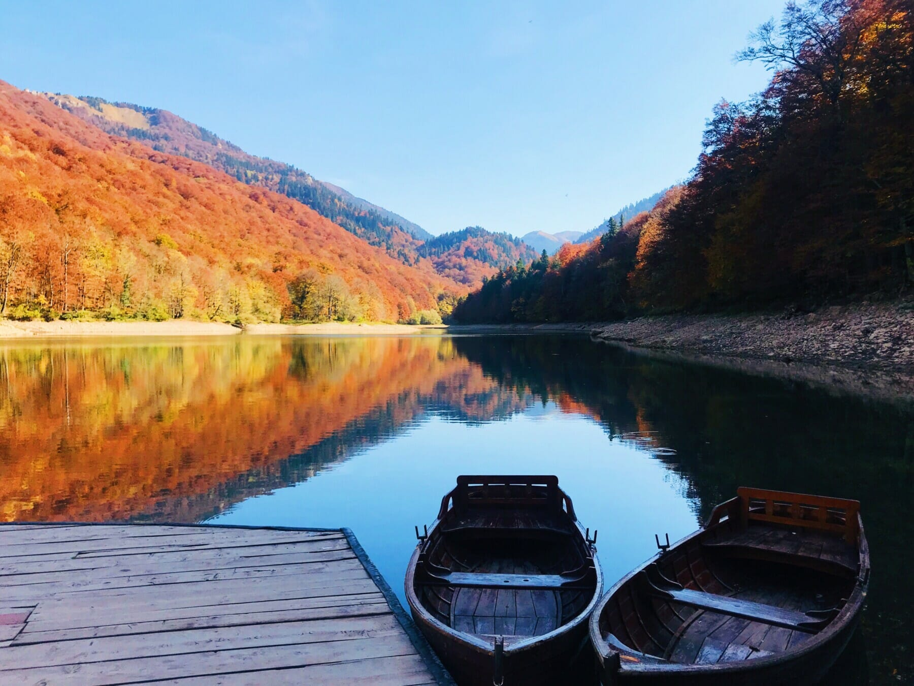 Boats on the reflective Biograd lake in NP Biogradska gora in Montenegro