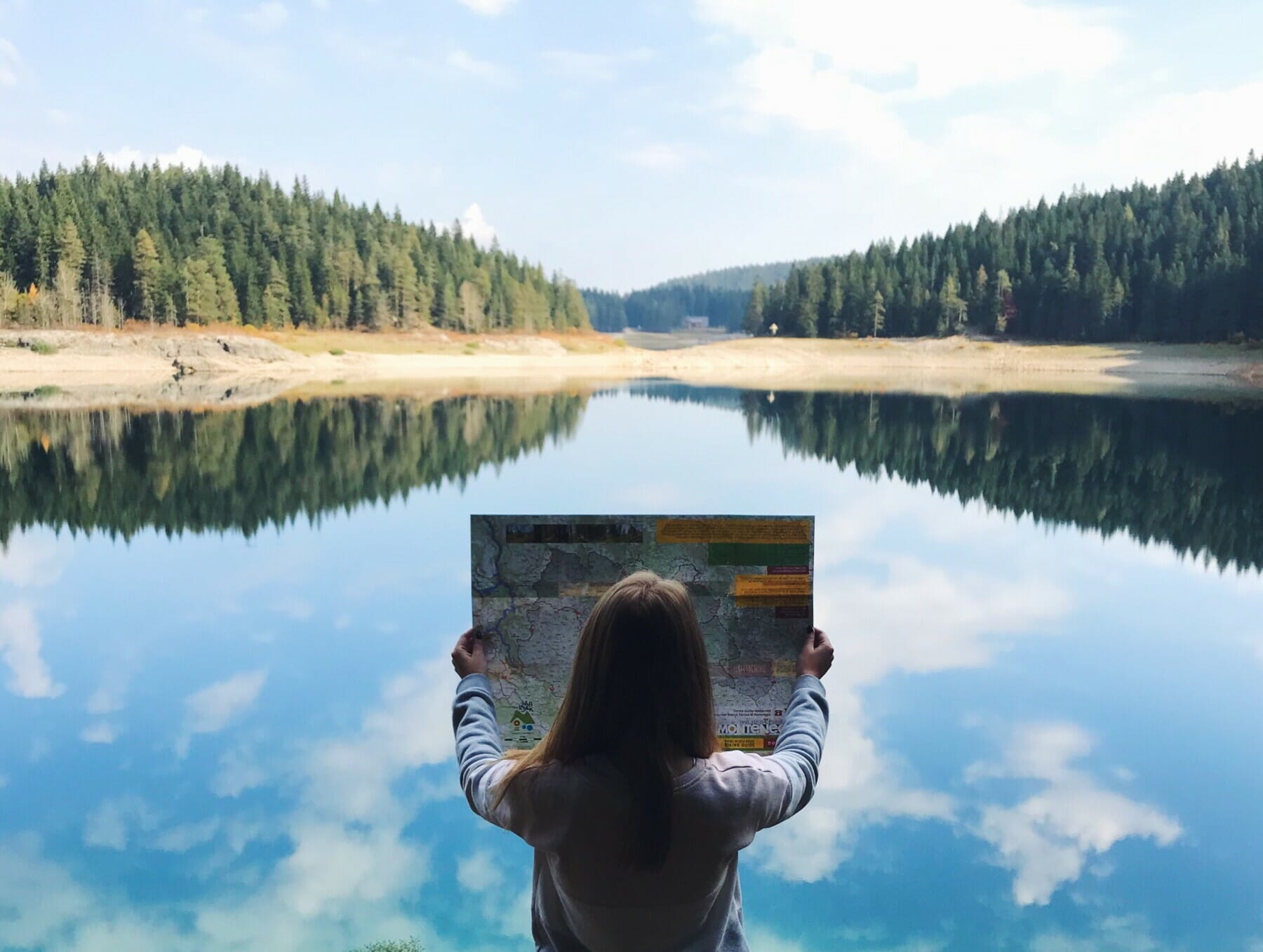 Girl with hiking map surrounded by lake and forest, Black Lake
