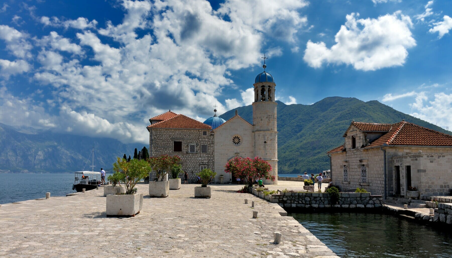 the church of our lady of the rocks on a blue sky with clouds and mountains montenegro adventure